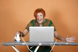 Older woman looking at a laptop computer on an ironing-board, and is evidently very pleased