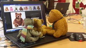 Three teddy bears are sitting on a laptop keyboard, staring at a Google Images display of teddy bears