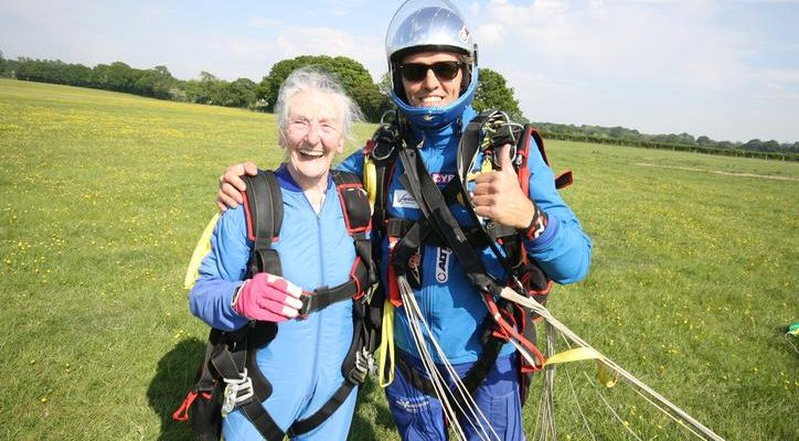 Irene with her youthful instructor, both wearng parachute gear. They are on the ground after landing, still attached to the parachute cords