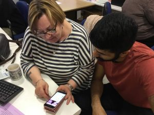 FCA volunteer Karanbir is helping Janet with her phone
