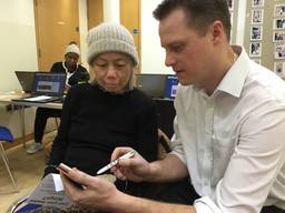 Scene at Whitmore Community Centre - Mike shows Serena something on her smartphone
