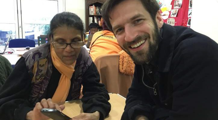 Hardeep checking her phone, with help from volunteer Nick